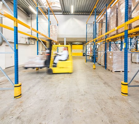 Factory worker driving forklift truck